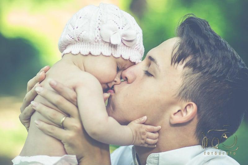 padre con bebé cogido y dándole un beso