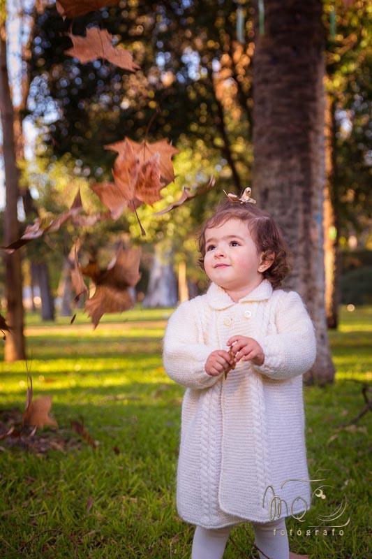 niña de pié en el parque mirando hojas en el aire