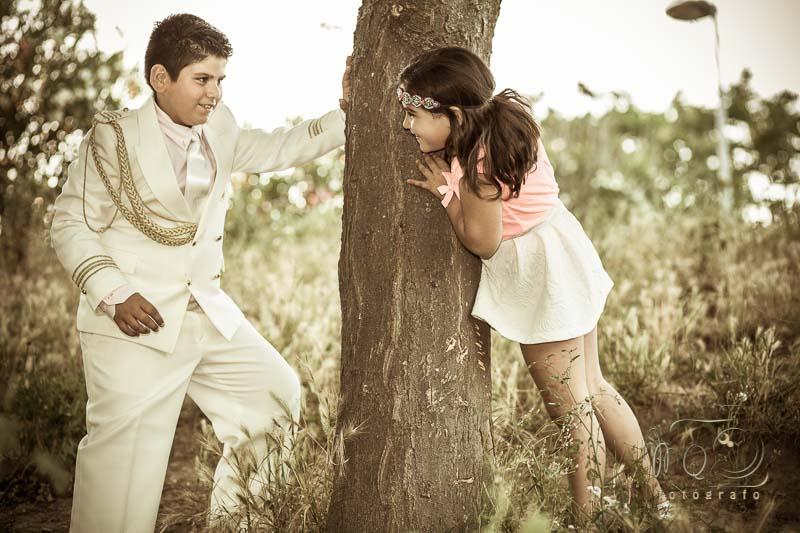 niño de comunión jugando con la hermana tras un arbol