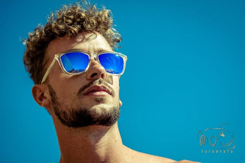 retrato de chico con pelo rizado y gafas de sol azules