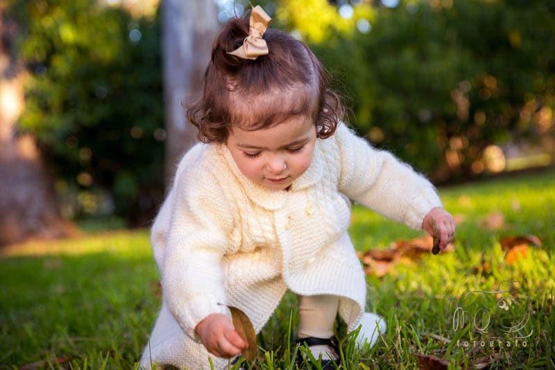 niña en el parque agachada cogiendo hojas del suelo