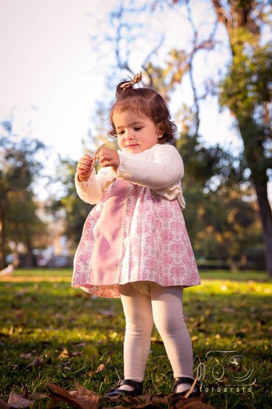 niña Aldara de pié en el parque con una hoja en las manos