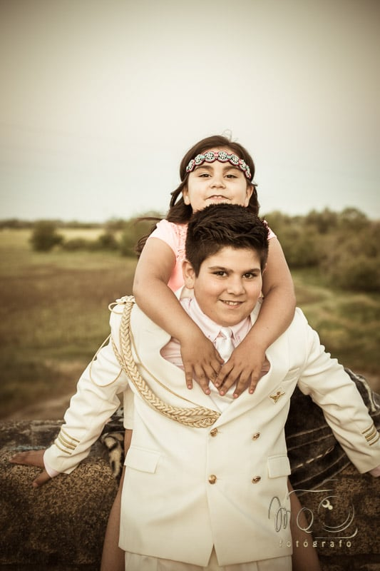niño de comunión con su hermana a la espalda