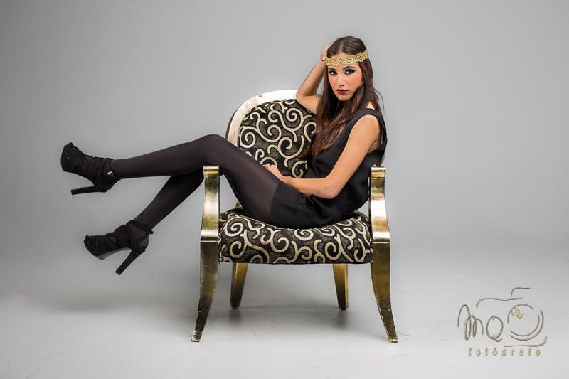 chica con vestido y medias negras, inclinada sobre sillón