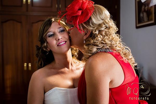 Madre besando a la hija vestida de novia