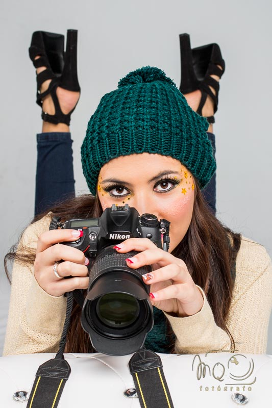 Modelo con cámara de fotos y gorro verde