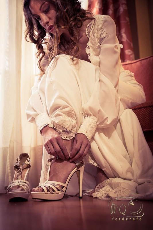 novia sentada en silla abrochándose el zapato