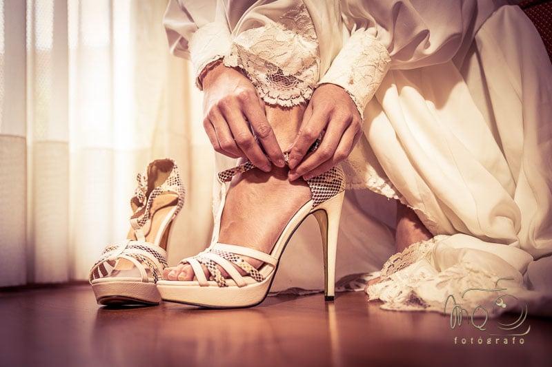 detalle de novia abrochándose el zapato