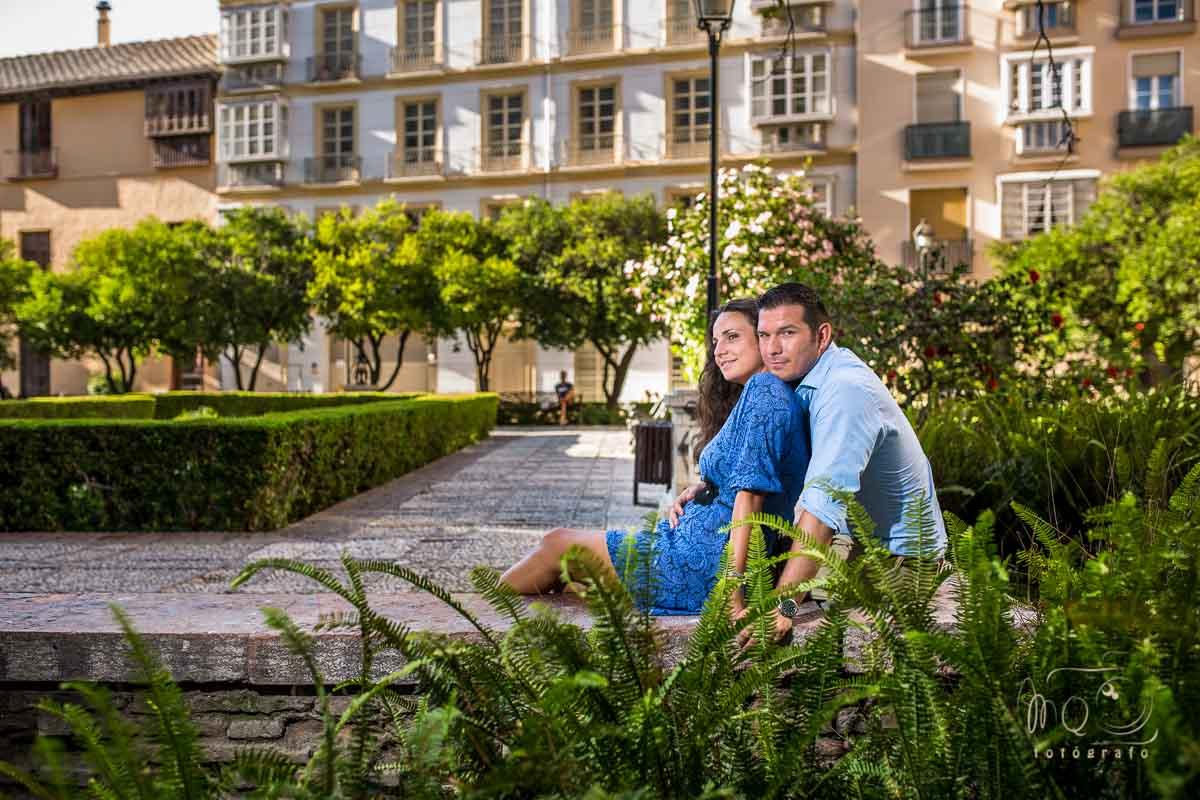 novios sentados en el patio de los naranjos de la catedral de Málaga, abrazados, en su preboda