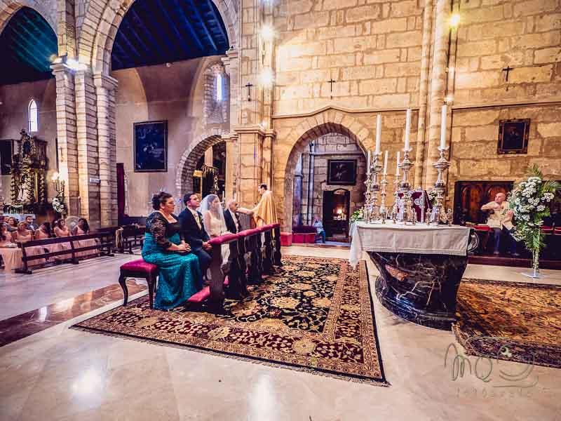 paraje y padrinos en el altar de una iglesia en su boda