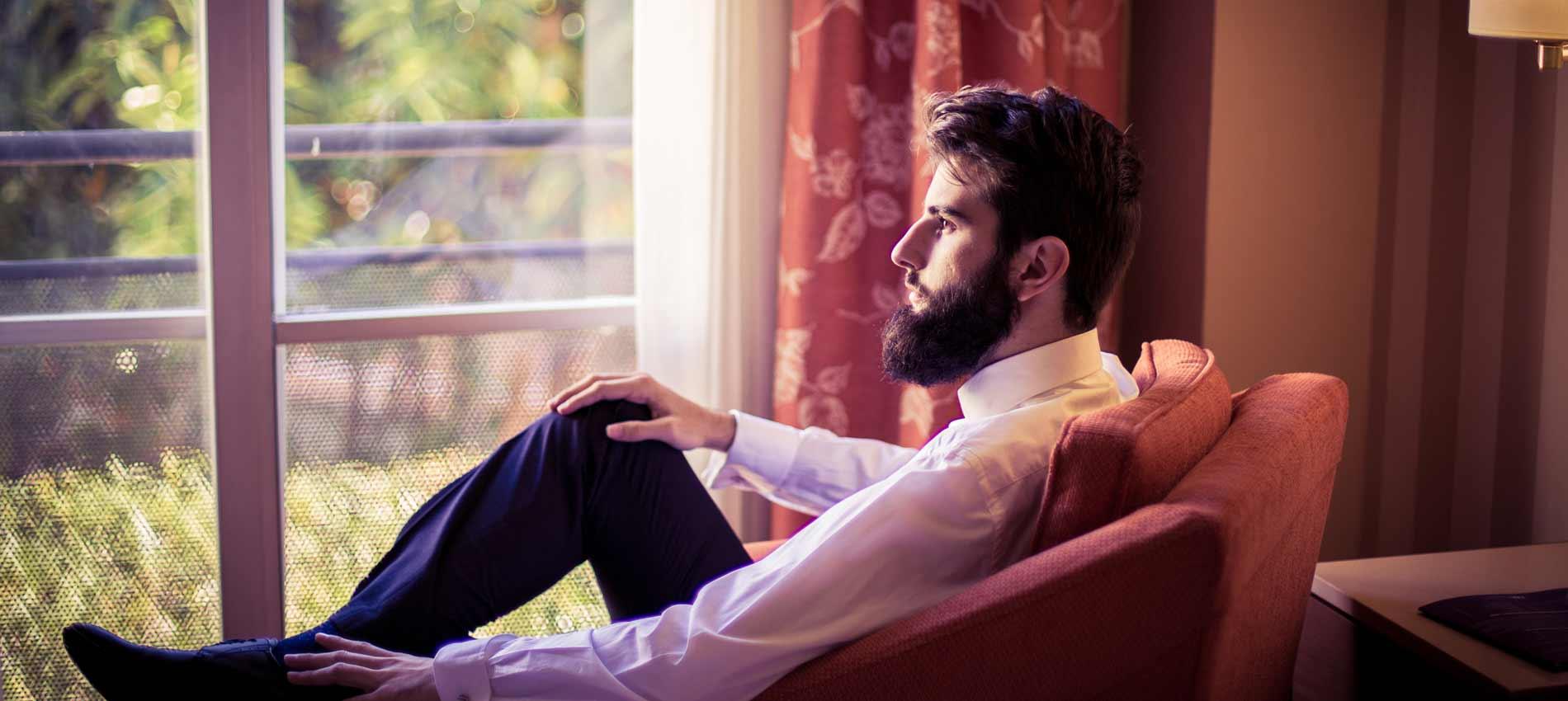 novio sentado frente a una ventana en los preparativos de boda