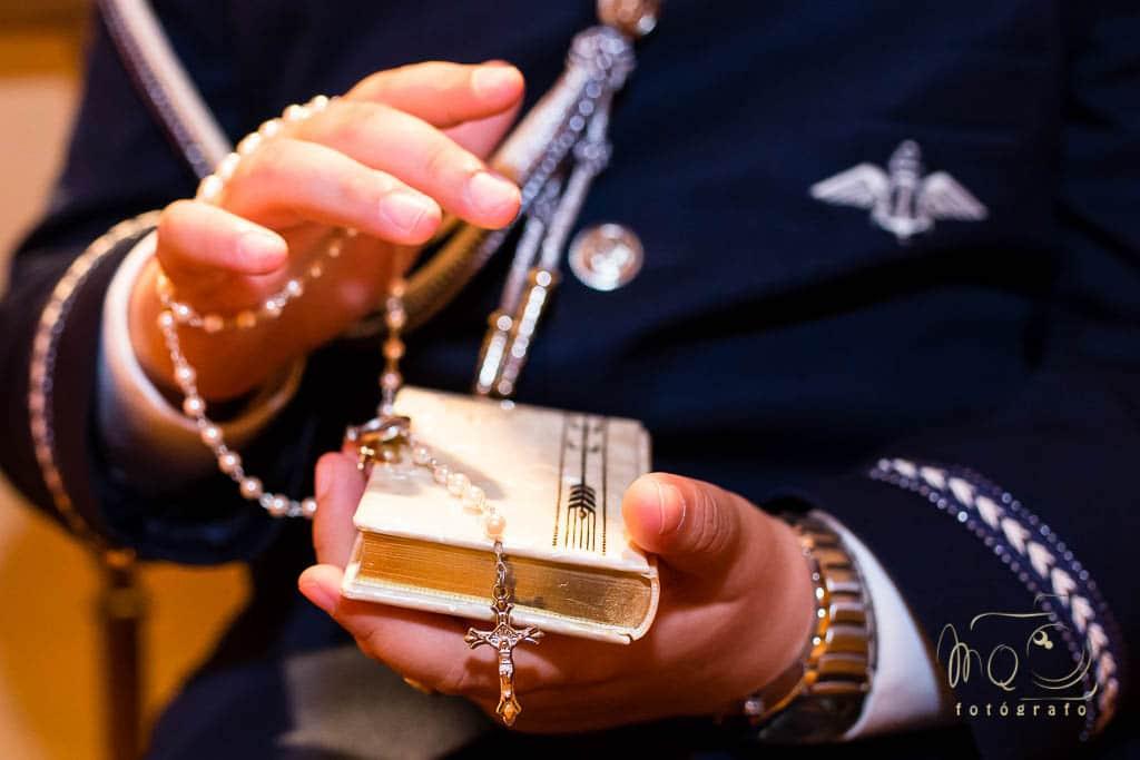 Manos con libro de comunión y rosario