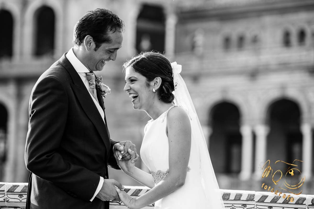 pareja de novios cogidos de la mano riéndose, en plaza de España Sevilla