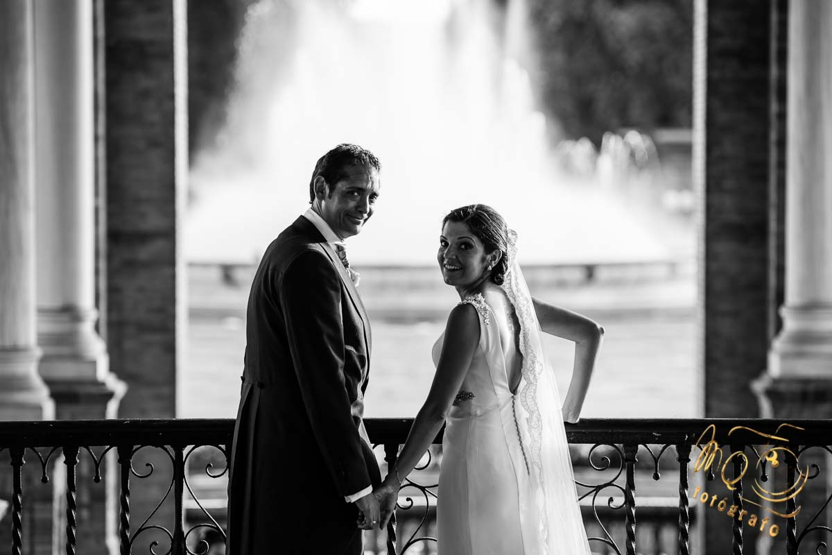 pareja de novios cogidos de la mano mirando hacia atras, en entreda de la plaza de España Sevilla con fuente al fondo