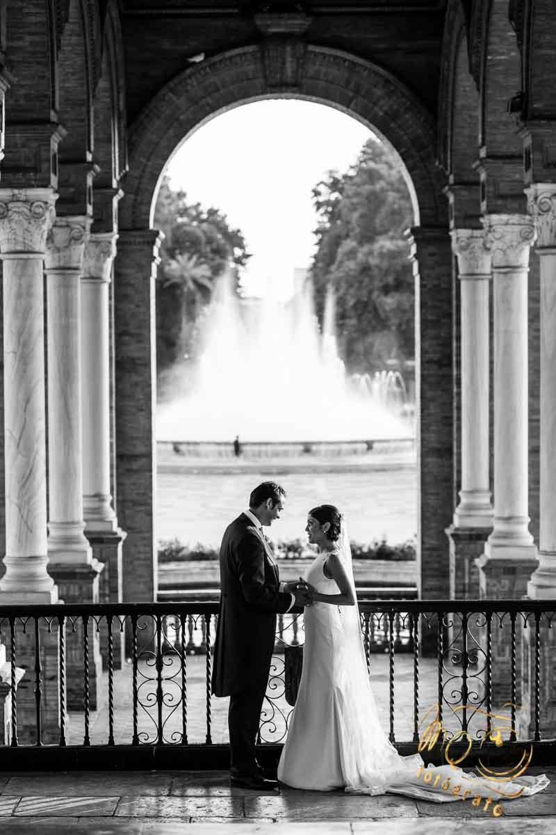 pareja de novios cogidos de la mano entre columnas de la plaza de España Sevilla