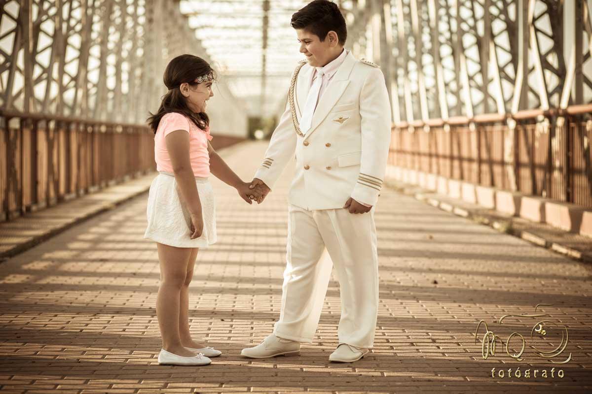 Niño de Comunión de la mano con su hermana en un puente de hierro