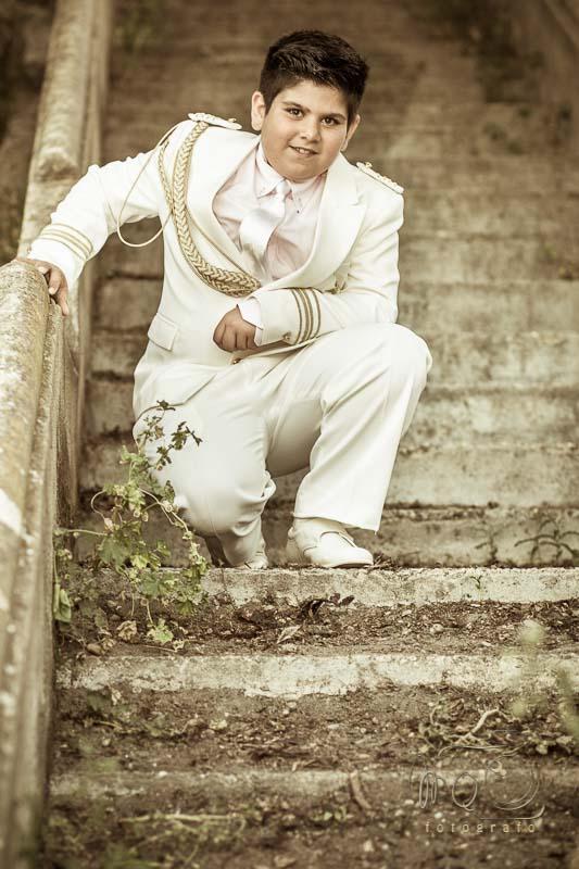 Niño de comunión agachado en escalera