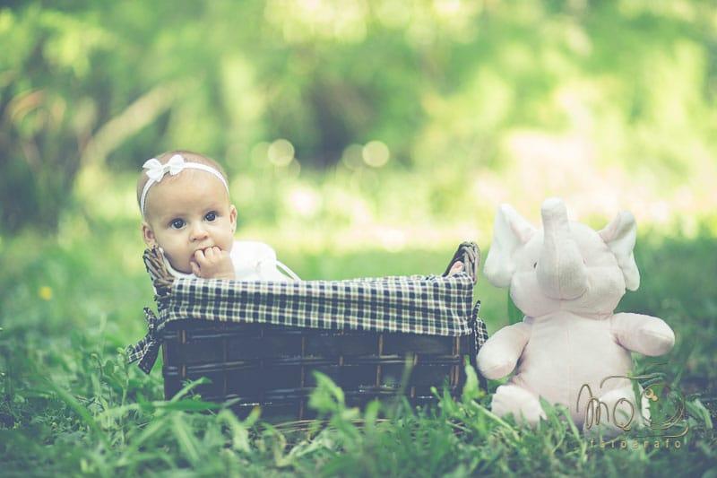 niña Aldara dentro de canasta sobre el cesped