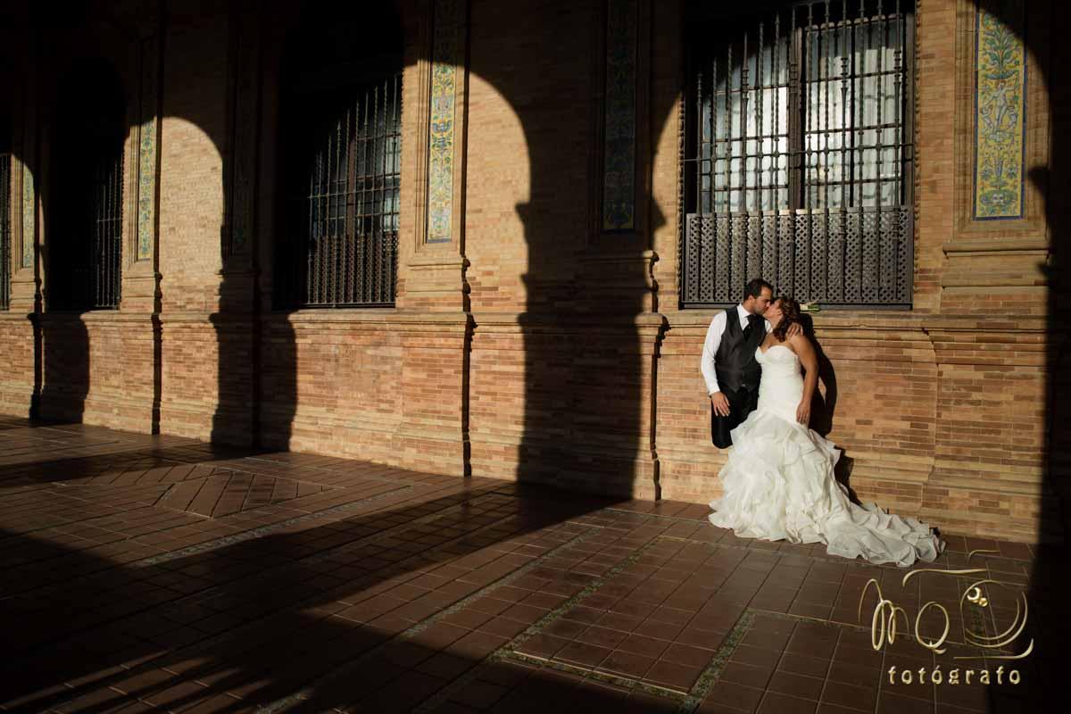 Reportajes de boda en Sevilla y Córdoba con una Pareja de novios besandose en pasillo de plaza de España de Sevilla
