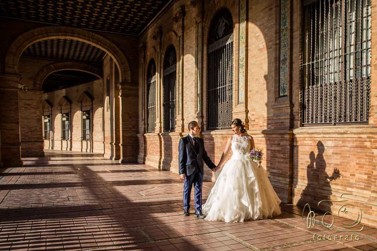 pareja de novios andando de la mano en pasillo de la plaza de España en Sevilla