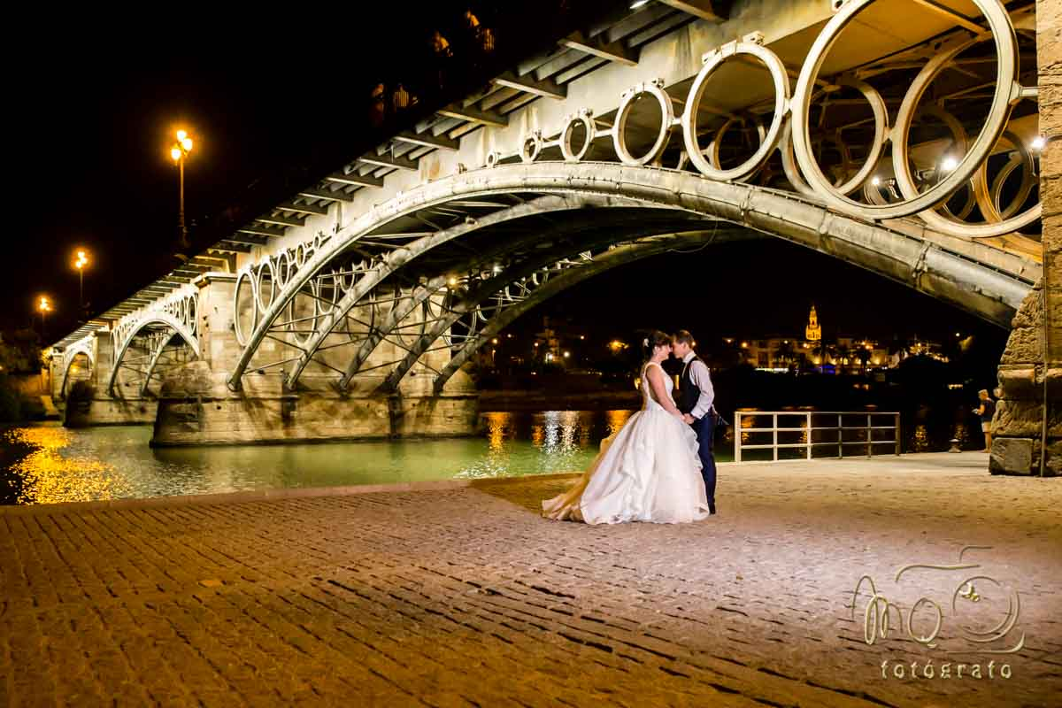pareja de recien casados besándose bajo puente de Triana en Sevilla de noche
