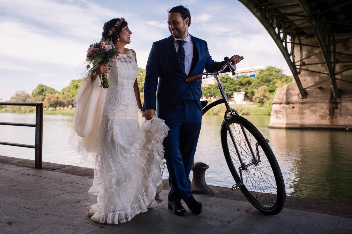 Pareja de novios con una bicicleta bajo el puente de Triana de Sevilla