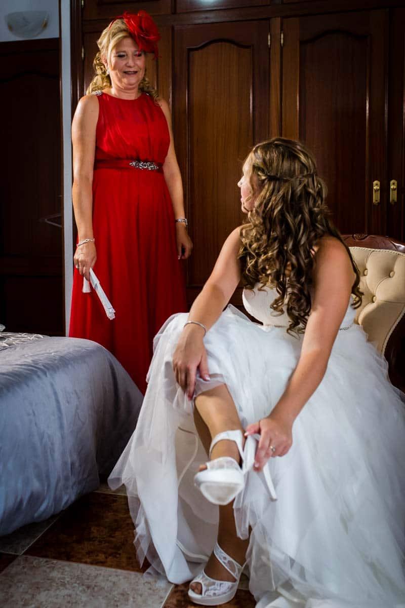 novia sentada con vestido de Vertiza Gala poniendose zapatos de Calenda