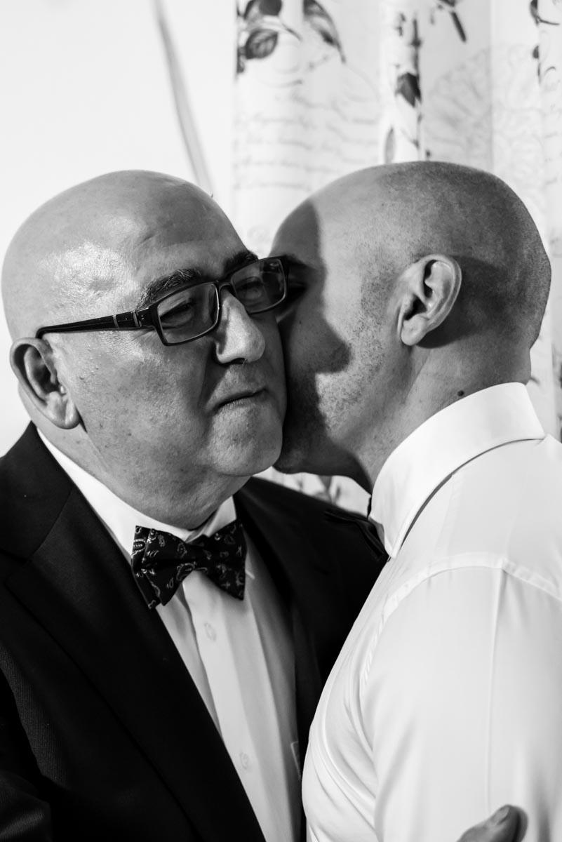 padre besando al novio en su habitación