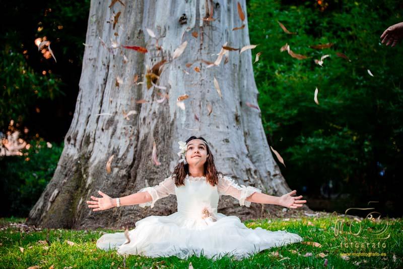 niña de comunión sentada lanzando hojas al aire