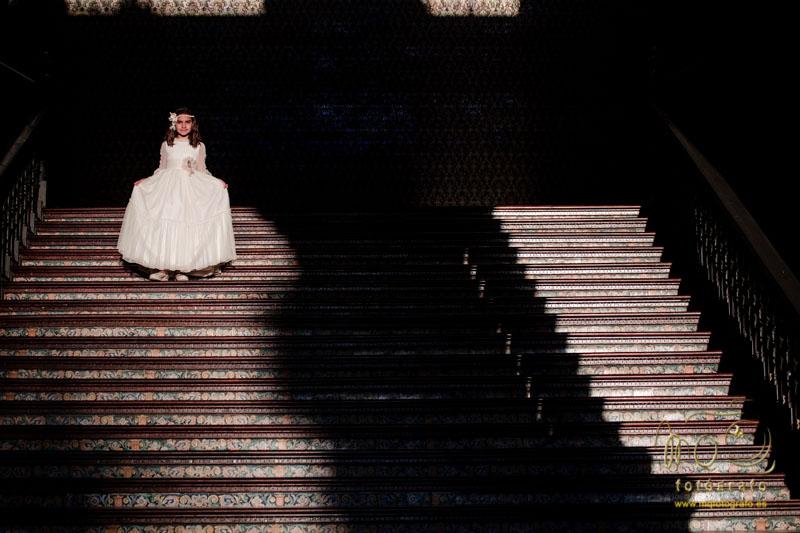 niña de comunión en escaleras