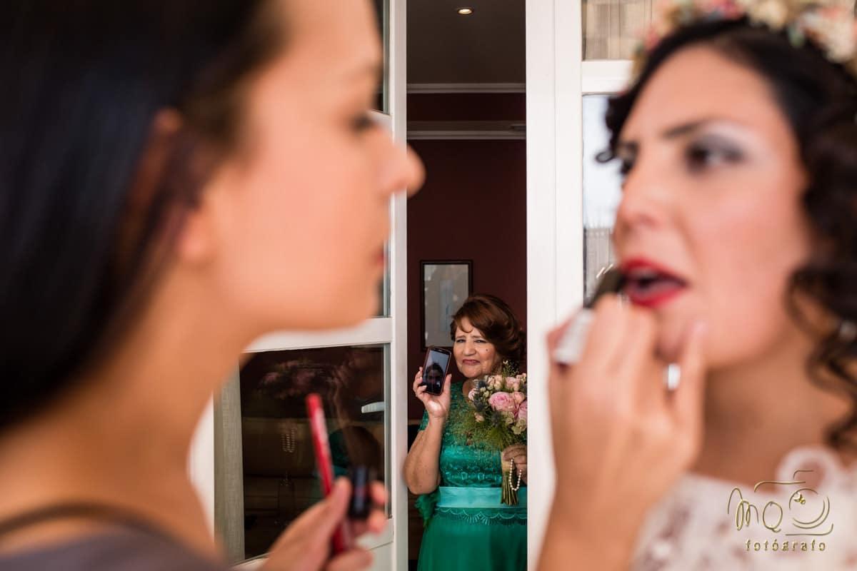 madre de la novia al fondo con el teléfono móvil mientras maquillan a la novia en primer plano