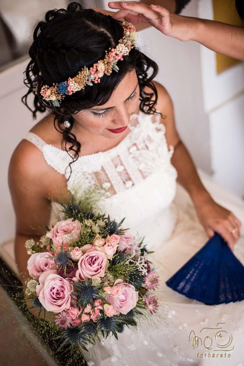 novia sentada mirando al suelo con el ramo de novia en la mano