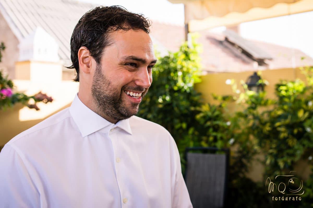 novio sonriendo con una camisa blanca puesta