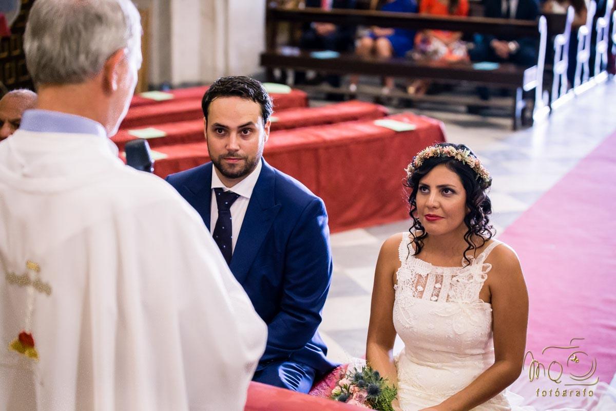 novios en al altar mirando al sacerdote