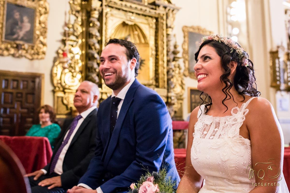 novios riéndose en el altar
