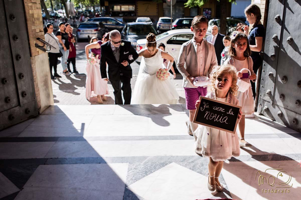 novia entrando a la iglesia de la mano del padre y niña con cartel ya viene la novia