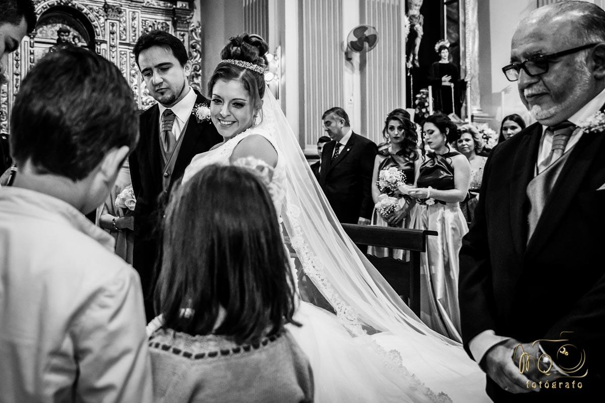 Novios en el altar de la parroquia mirándo a la niña que trae los anillos