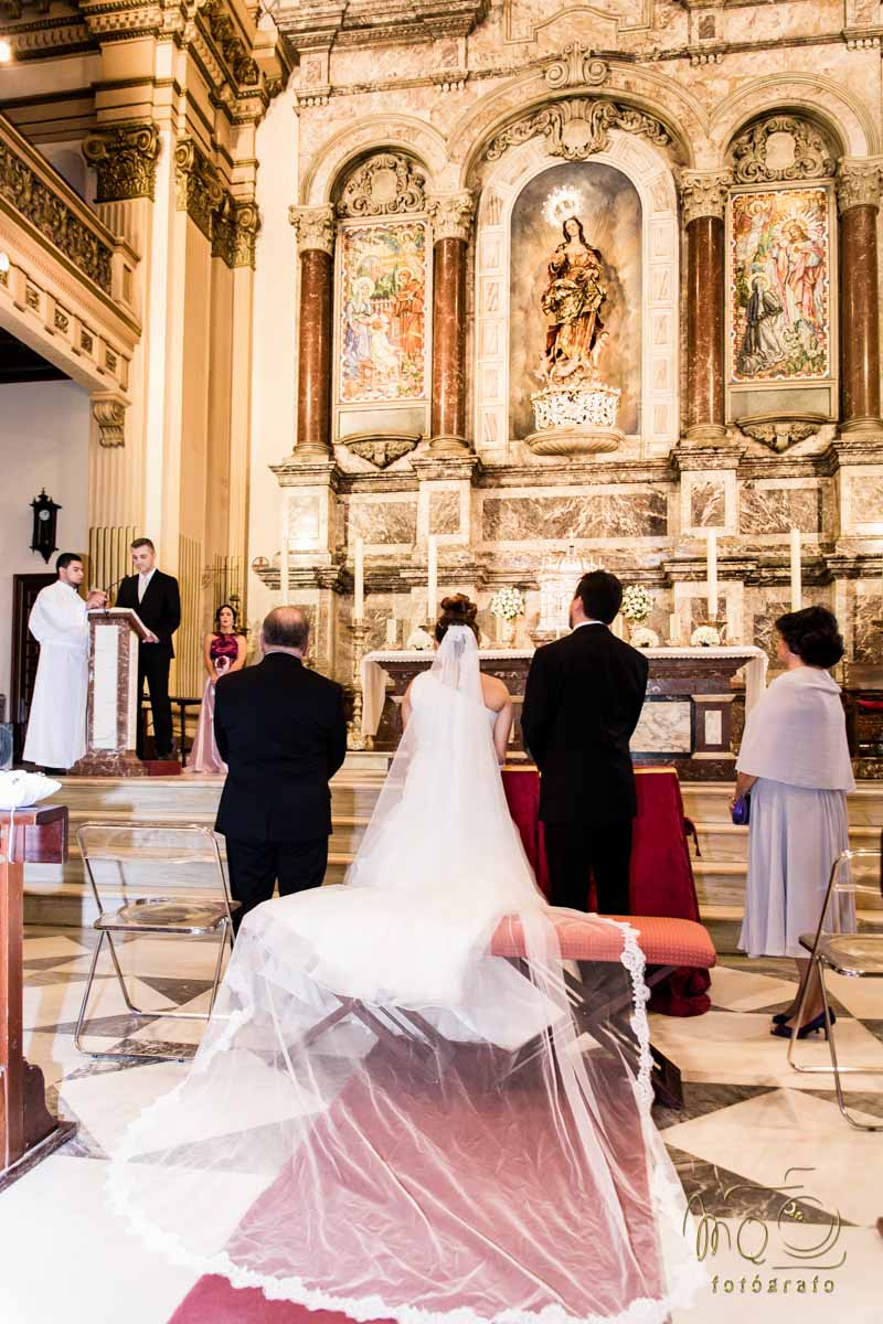 novios en el altar mirando a quien habla en el atril
