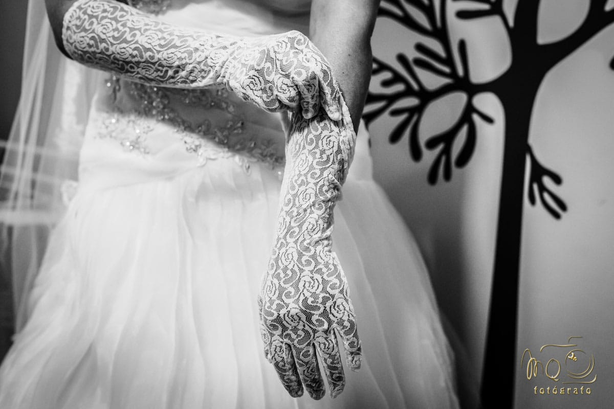 Novia poniéndose guantes blancos de hilo