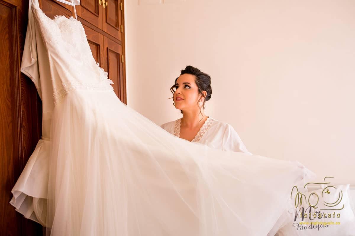 novio extendiendo el vestido de novia colgado