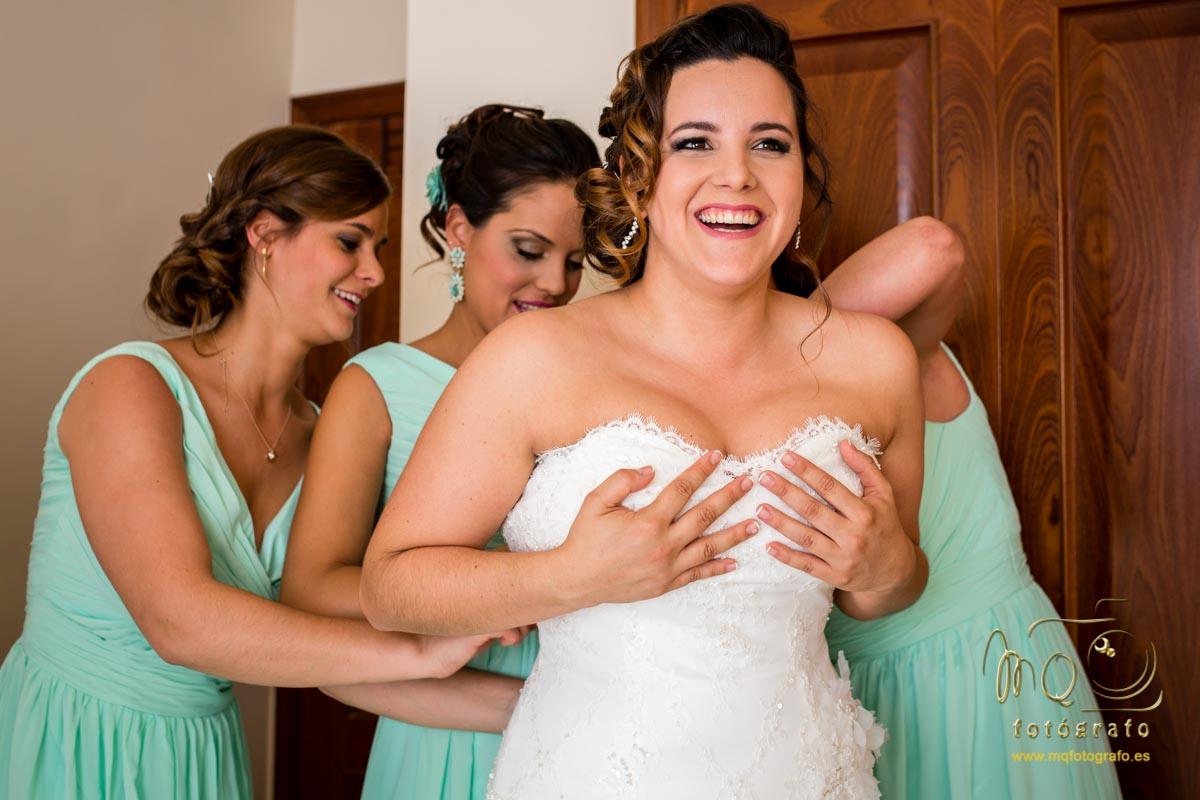 damas de honor abrochando por detrás el vestido a la novia