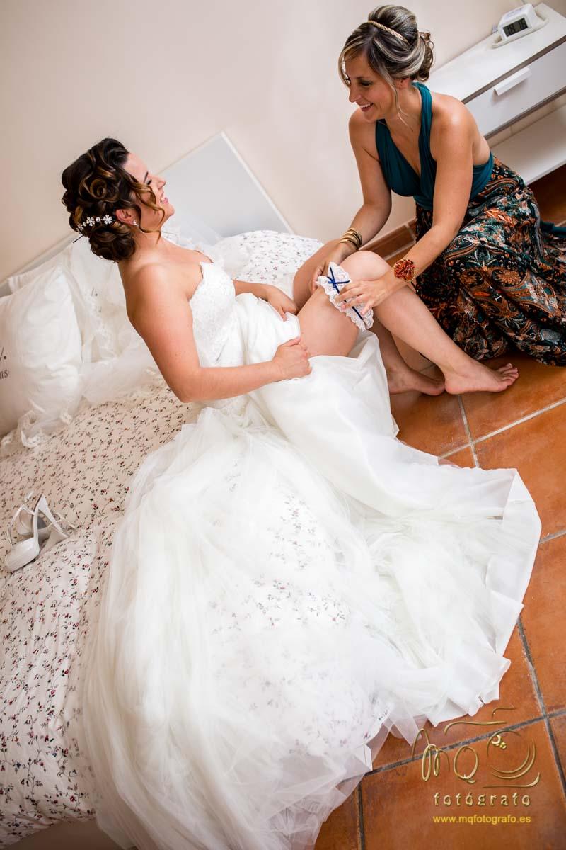 novia sentada en la cama con el vestido extendido y la hermana agachada poniéndole la liga