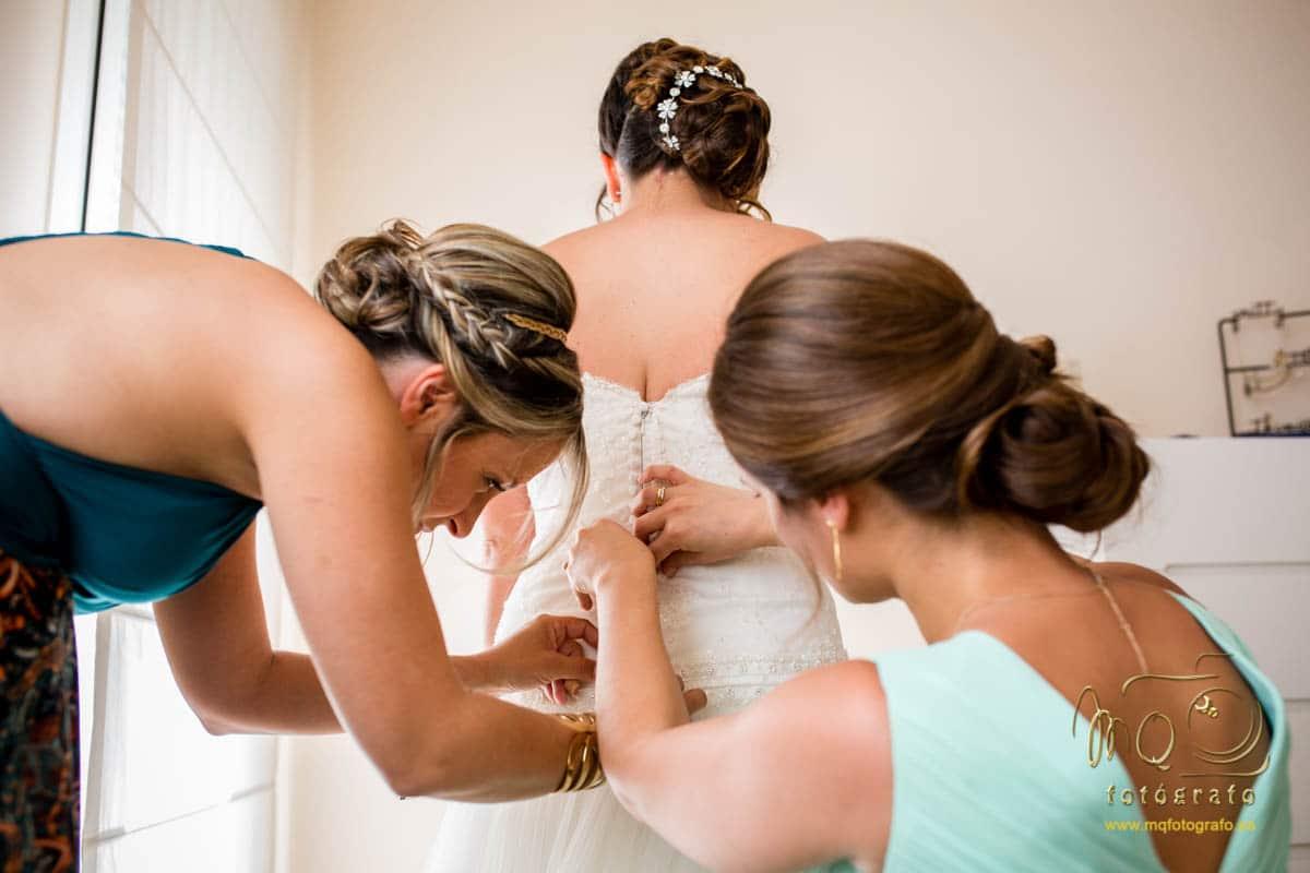 Damas de honor abrochando el vestido a la novia, detrás de ella