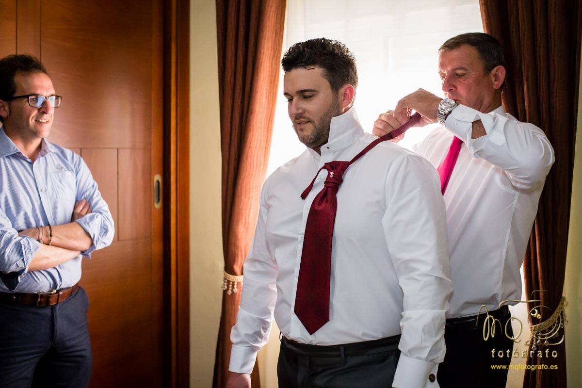 padre poniendo la corbata al novio y el sastre mirando
