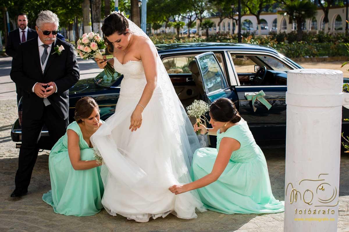 novia al bajar del coche y las damas poniendo bien el vestido