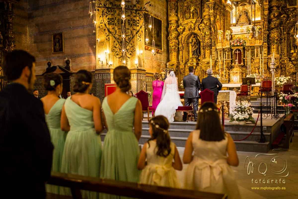 vista desde la tercera fila de asientos, se ve a las damas de honor y a los novios y padrinos en el altar
