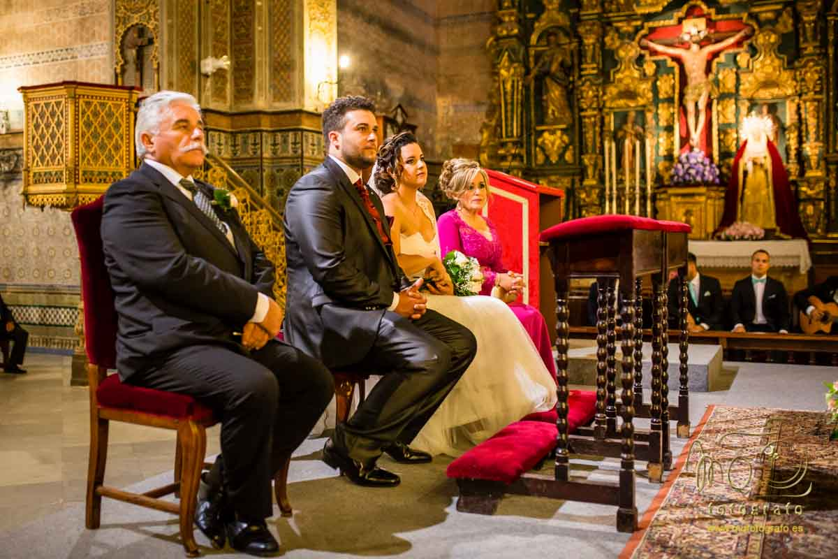 vista lateral de las novios y los padrinos sentados en el altar