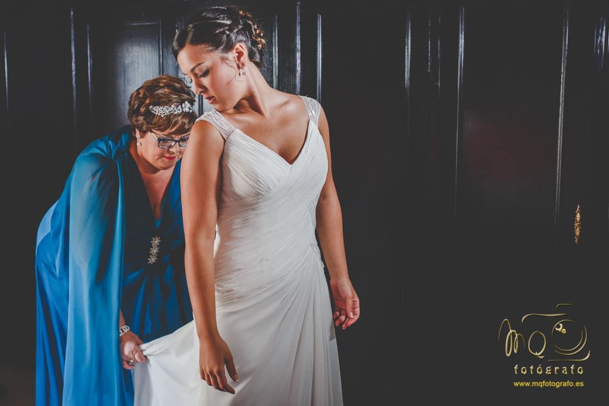 madre de la novia colocándole el vestido