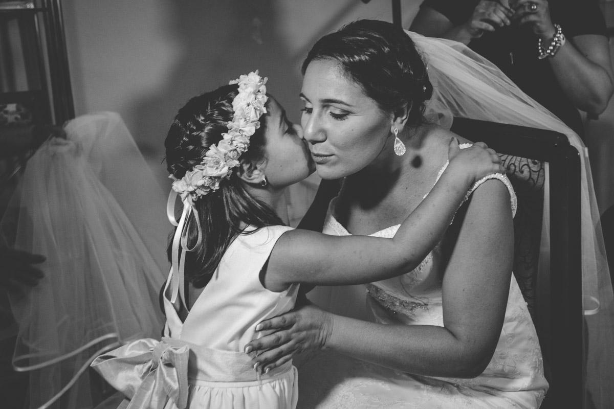 hija besando en la cara a la novia, su madre
