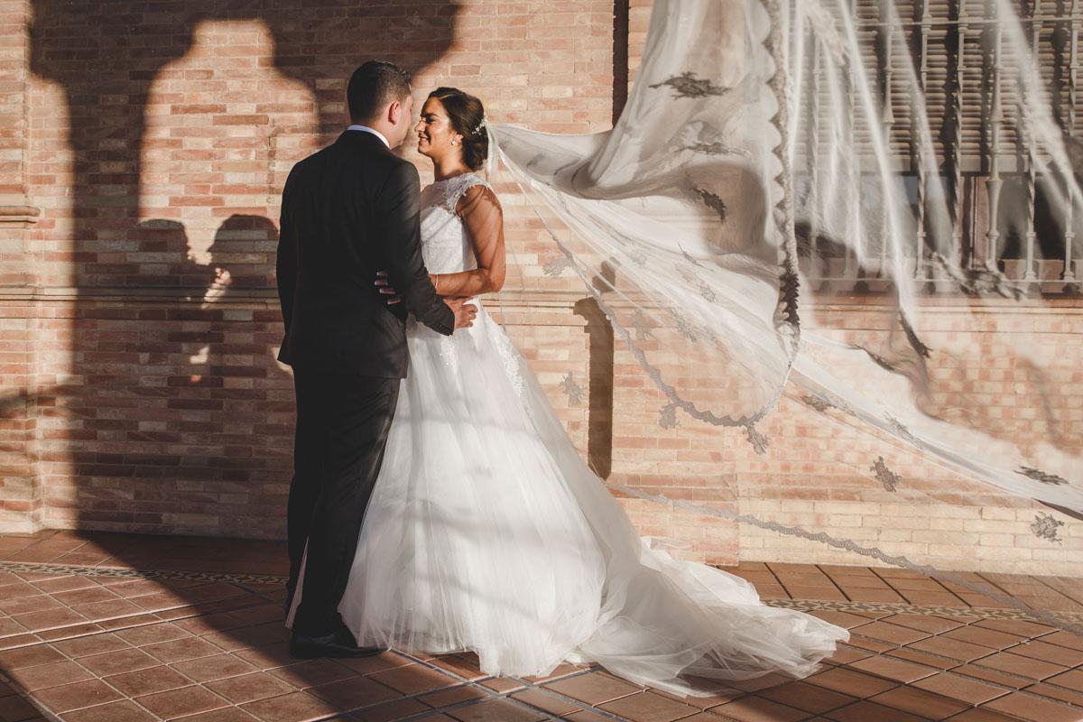 novios besándose en plaza de España con velo al aire